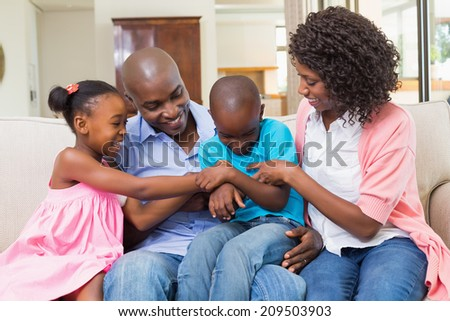 Happy family relaxing on the couch at home in the living room - stock photo