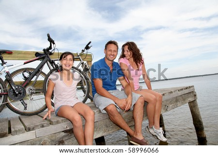 Happy family resting on a pontoon - stock photo