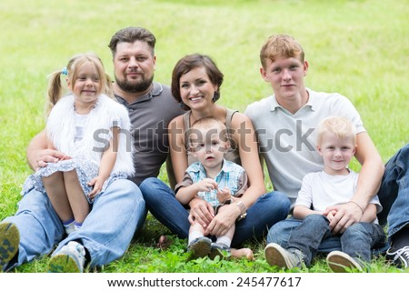 Happy family resting on the grass in the park - stock photo