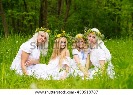 Happy family resting on the nature in the summer. Mom and daughter with wreath in the flowers in the park. Girls sitting in the park on the grass - stock photo