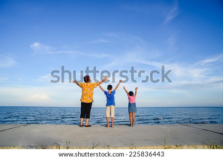 Happy family rises hands at Pranburi beach.  Prachuabkirikhan, Thailand. - stock photo