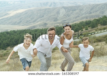 Happy family running in summer mountains - stock photo