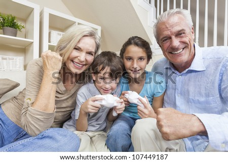 Happy family, senior adults & children, grandparents, grandson and granddaughter, having fun playing video console games together. - stock photo