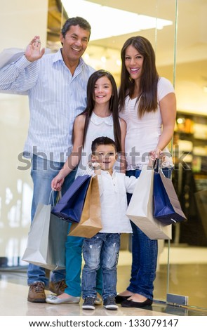 Happy family shopping and holding bags at the mall - stock photo