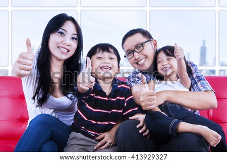 Happy family showing thumbs up at apartment - stock photo