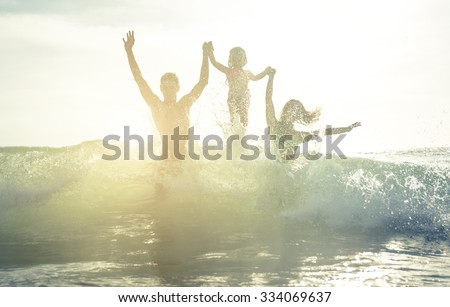 Happy family silhouette in the water. Jumping between the waves - stock photo