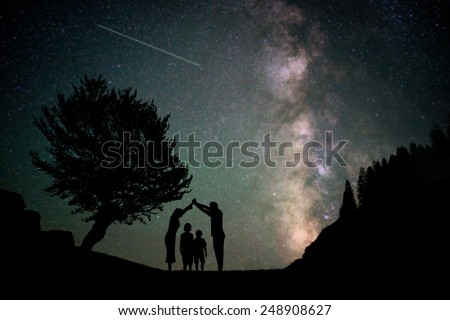 Happy family silhouette with Milky Way and beautiful night sky full of stars in background making house shape for care and love concept - stock photo