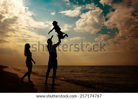 happy family silhouettes on beach at sunset - stock photo