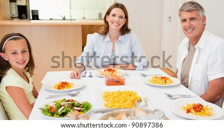 Happy family sitting at dinner table together - stock photo