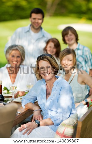 happy family sitting at table and having a garden party - stock photo