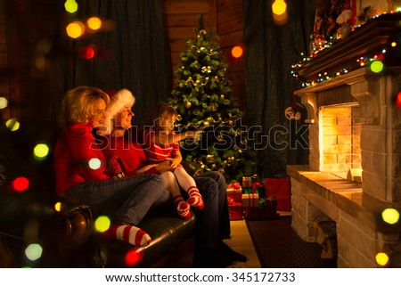 Happy family sitting by fireplace at Christmas tree.  Child shows on fire.  - stock photo