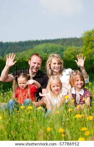 Happy family sitting in a meadow full of dandelions in spring - stock photo
