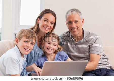 Happy family sitting on a couch using a laptop in a living room - stock photo