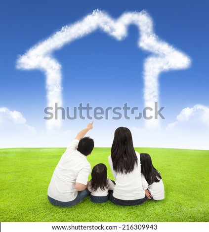 happy family sitting on a meadow with house of clouds in the blue sky - stock photo