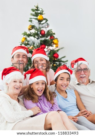 Happy family sitting on couch at christmas - stock photo