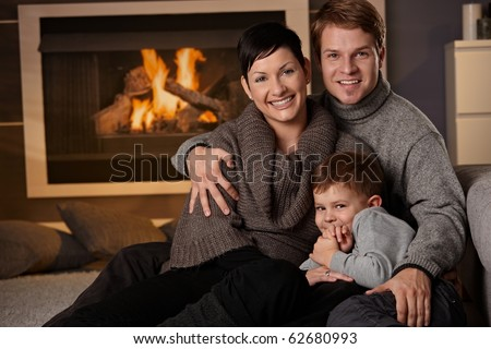 Happy family sitting on couch at home in a cold winter day, looking at camera, smiling. - stock photo