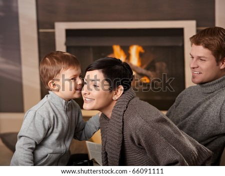 Happy family sitting on couch at home in front of fireplace, looking at camera, smiling.? - stock photo