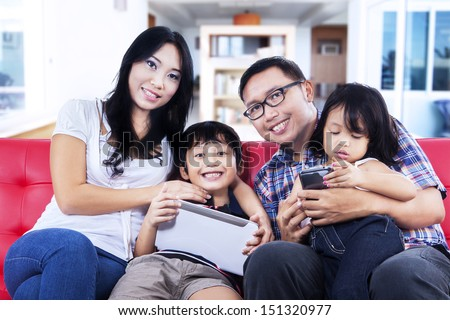 Happy family sitting on red sofa at home - stock photo
