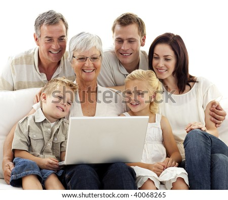 Happy family sitting on sofa using a laptop in living-room - stock photo