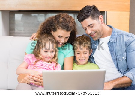 Happy family sitting on sofa using laptop together at home in living room - stock photo