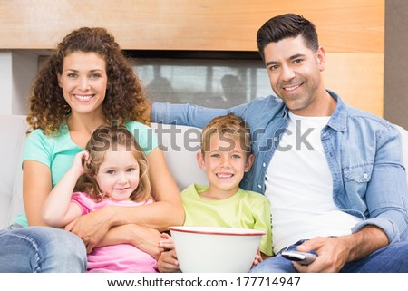 Happy family sitting on sofa watching tv with popcorn at home in living room - stock photo