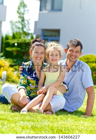 Happy family sitting on the lawn in front of his new cottage - stock photo