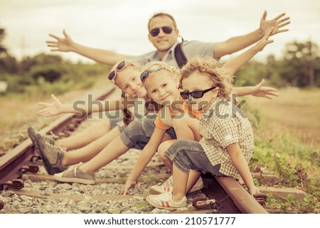 Happy family sitting on the railway at the day time. Concept of friendly family. - stock photo