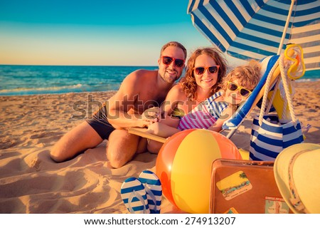 Happy family sitting on the sunbed. Man, woman and child having fun at the beach. Summer vacation concept - stock photo