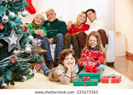 Happy family sitting with gifts at christmas tree at home - stock photo