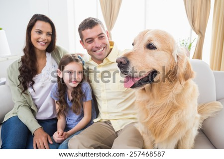 Happy family sitting with Golden Retriever on sofa at home - stock photo
