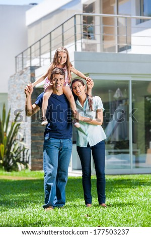happy family smile in front of house outdoor, parents with child daughter - stock photo
