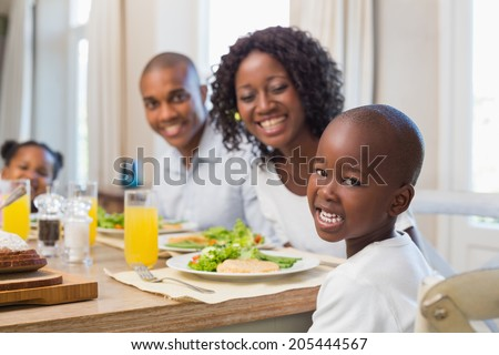 Happy family smiling at camera at lunch at home in the kitchen - stock photo