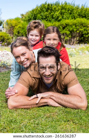 Happy family smiling at camera in the countryside - stock photo