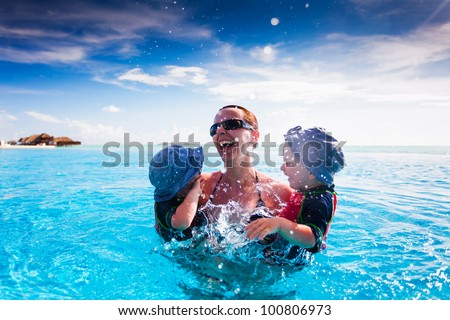 Happy family splashing in blue swimming pool on a tropical resort - stock photo