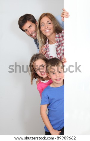 Happy family standing by whiteboard - stock photo