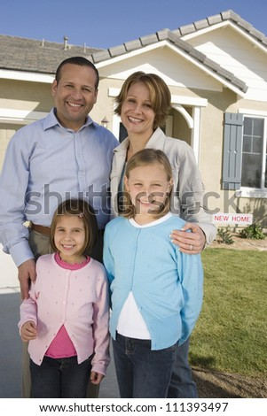 Happy family standing in front of new house - stock photo