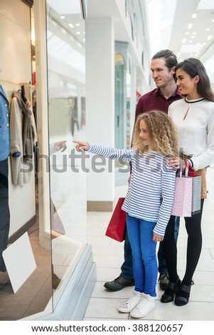 Happy family standing in front of shop window and looking at the apparels - stock photo