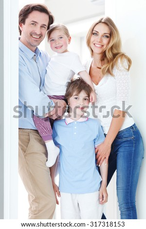 happy family standing inside their new house - stock photo