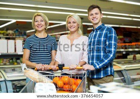Happy family standing near display with frozen food in shop - stock photo