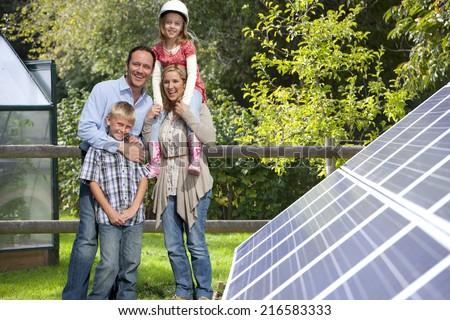 Happy family standing near large solar panels - stock photo