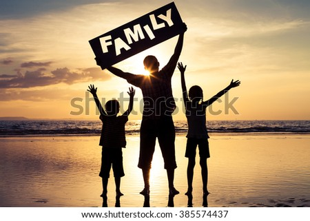 """Happy family standing on the beach at the sunset time. Parents hold in the hands  inscription """"Family"""". Concept of happy family. - stock photo"""