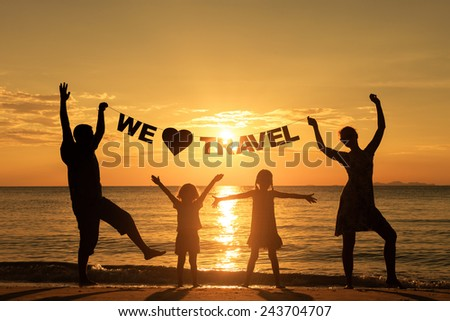 "Happy family standing on the beach at the sunset time. Parents hold in the hands  inscription ""We love travel"". Concept of friendly family. - stock photo"