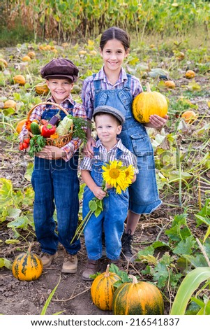Happy family standing with vegetables on pumpkin's field - stock photo