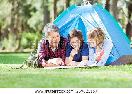 Happy family studying map while lying in tent at park - stock photo