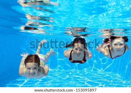 Happy family swim underwater in pool and having fun, mother and children on vacation  - stock photo