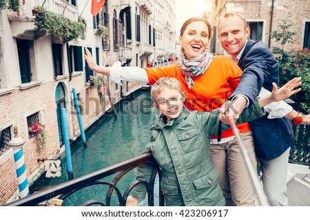 Happy family take a self photo on the one of bridges in Venice - stock photo