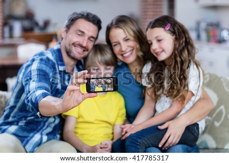 Happy family taking a selfie on mobile phone at home - stock photo