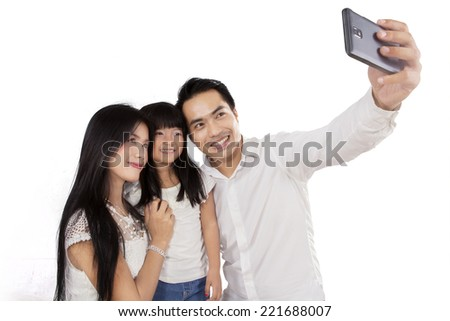 Happy family taking picture together in studio, isolated over white background - stock photo