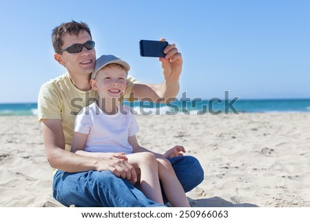 happy family taking selfie at the beach in california - stock photo