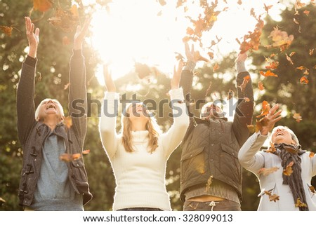 happy family throwing leaves around on an autumns day - stock photo